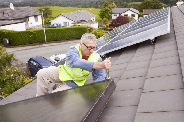 A workman fitting solar thermal panels for heating water, to a house roof in Ambleside, Cumbria, UK, that already has solar PV for generating electricity. © Global Warming Images / WWF-Canon